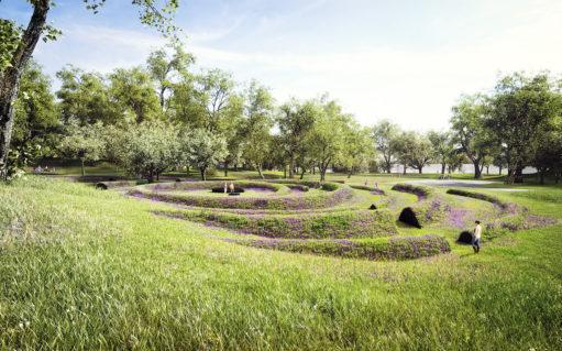 Monument af jord, græs og lilla blomster